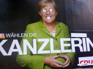 """Wir wählen die """"Unter-den-Teppich-Kehrerin"""", verfremdete ein unbekannter Plakatkünstler das Wahlplakat der neuen und alten Mutter der Nation."""